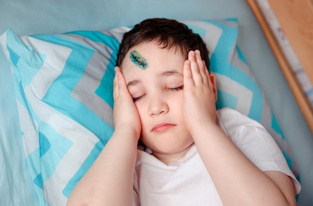 Het kind houdt zijn hoofd vast vanwege een ernstige hoofdpijn als gevolg van de verwonding. gekneusd, op het voorhoofd gesneden. de medische hechting werd uitgevoerd door een chirurg. veilige actieve recreatie