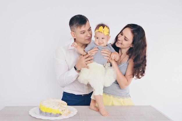 Het kind in de armen van zijn moeder en vader, die vervuild was met voedsel. een vrouw en een man met een kind in haar armen die cake eten