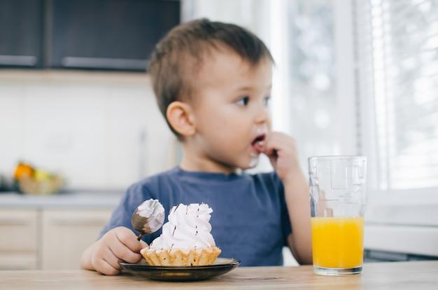 Het kind in de keuken eet een cake met slagroom