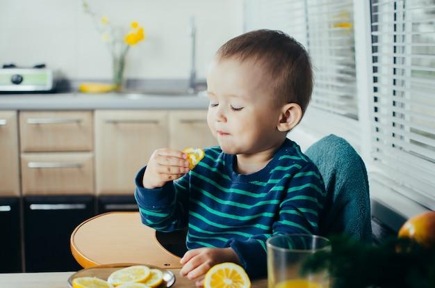 Het kind in de keuken eet een heerlijke, sappige citroen, gezond leven