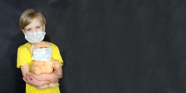 Het kind in een medisch masker met een stuk speelgoed draagt in zijn wapens op een zwarte muur. het spel van de dokter. het concept van bescherming tegen virussen en ziekten. stop het coronovirus. covid19. kopieer ruimte