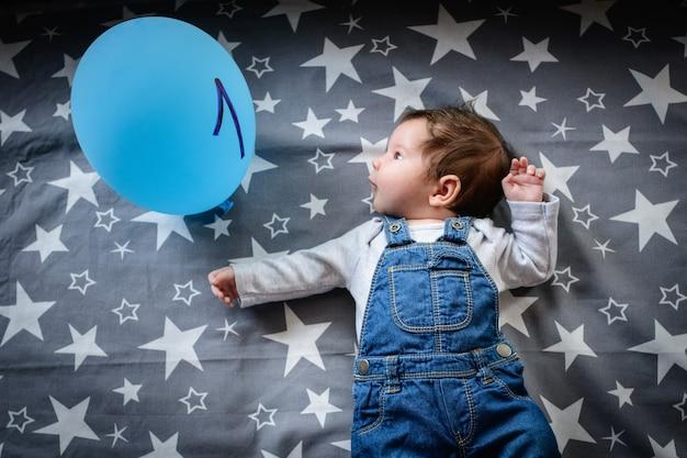 Het kind is een maand oud. een pasgeboren baby op de leeftijd van een maand ligt gelukkig. baby en bal met het opschrift in de vorm van een kleintje