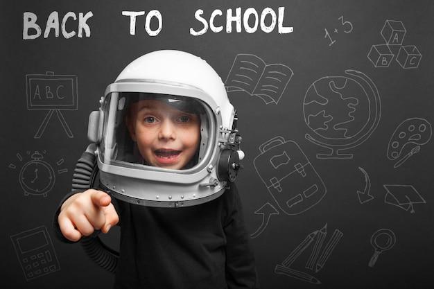 Het kind is van plan om terug naar school te gaan met een astronautenhelm om astronaut te worden