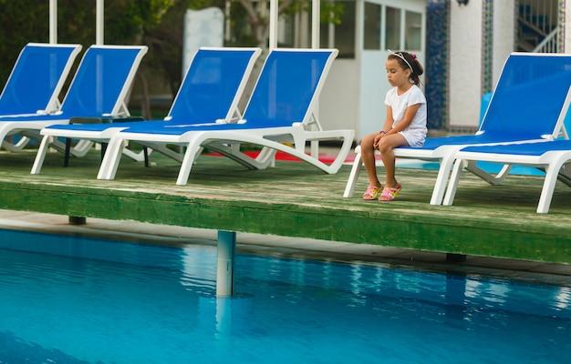 Het kind is verdrietig bij het zwembad