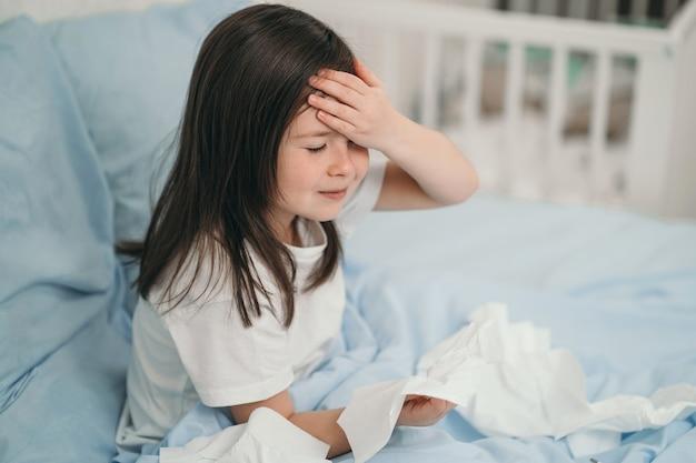 Het kind is verkouden en wordt thuis behandeld. het meisje heeft hoofdpijn. het kind is ziek en ligt in bed
