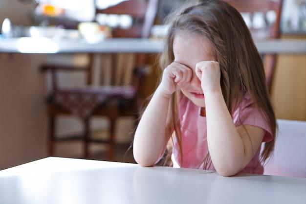 Het kind is verveeld, verdrietig gezicht. het meisje huilt. het concept van kindertijd, kinderdag, kleuterschool copyspace, slecht humeur, huisarrest, ongehoorzaamheid, ouderschap, overstuur, emoties