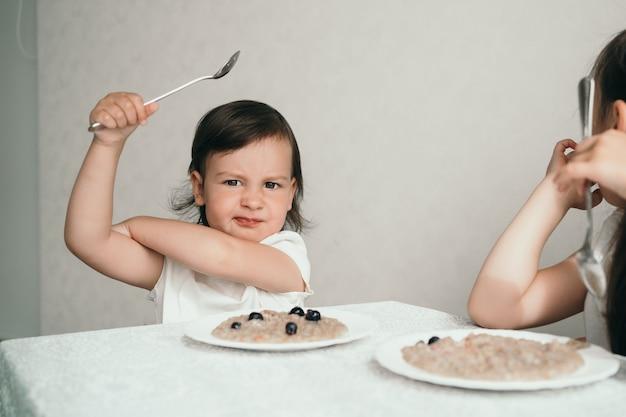 Het kind is wispelturig en weigert te eten. een klein meisje zit aan een tafel en is boos
