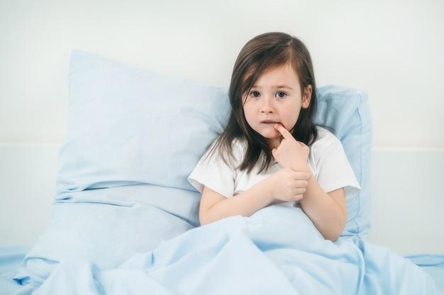 Het kind is ziek en ligt in bed. het meisje wordt voor verkoudheid behandeld. behandeling van kleine kinderen.