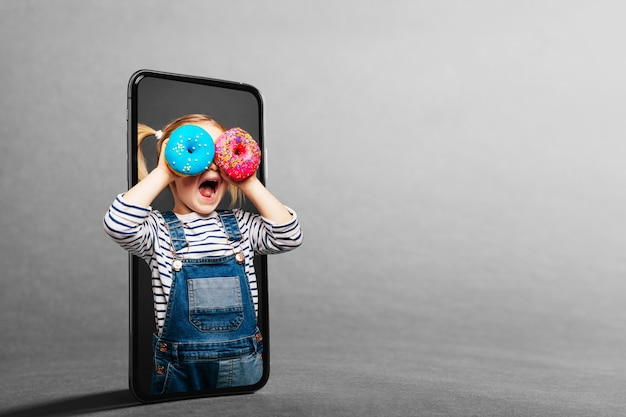 Het kind kijkt door de mobiele telefoon in een vergrootglas