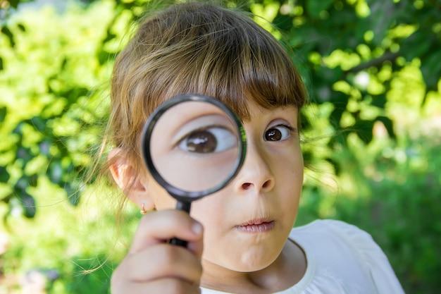 Het kind kijkt in een vergrootglas. toenemen. selectieve aandacht.