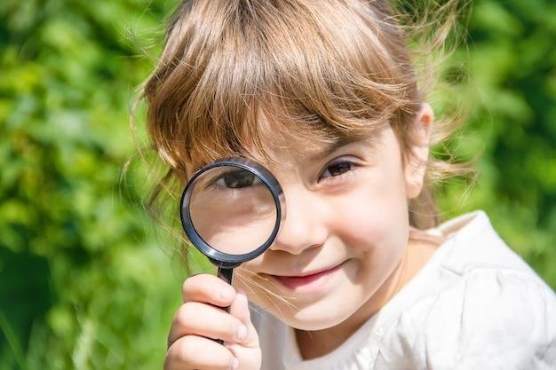 Het kind kijkt in een vergrootglas. toenemen.