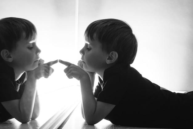 Het kind kijkt naar zichzelf in de spiegel op een donkere nacht