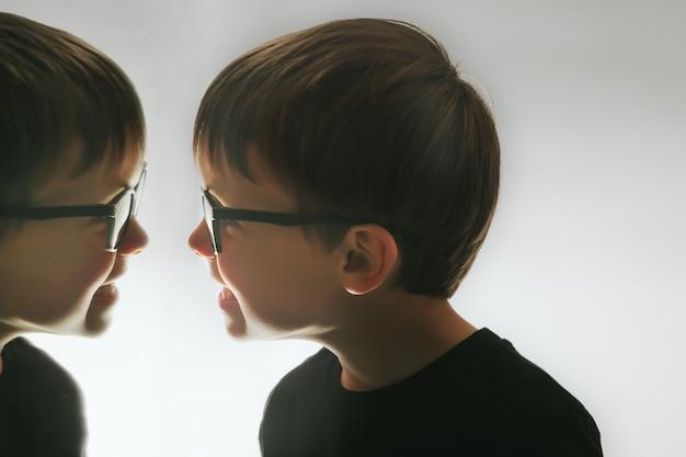 Het kind kijkt op een donkere nacht naar zichzelf in de spiegel