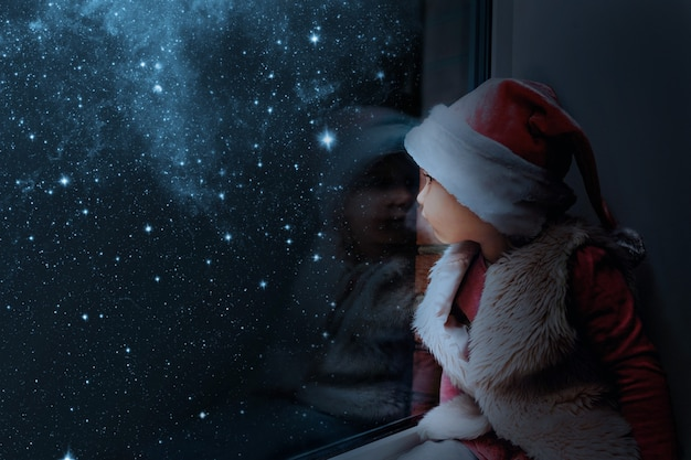 Het kind kijkt op eerste kerstdag uit het raam Premium Foto