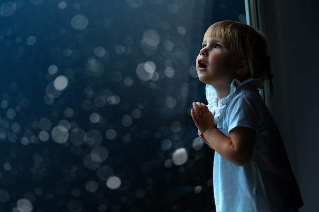 Het kind kijkt op eerste kerstdag uit het raam