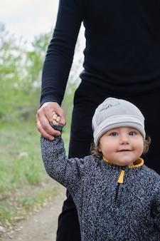 Het kind kijkt over de schouder van zijn vader. loop met zijn zoon in het park van de vader. vaderdag