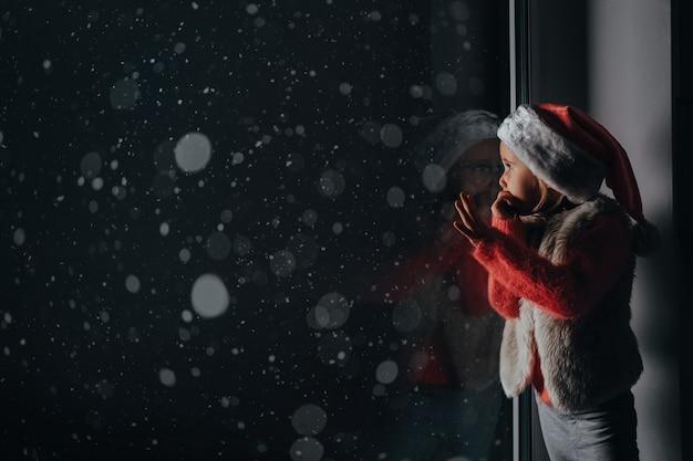 Het kind kijkt uit het raam op kerstmis van jezus christus.