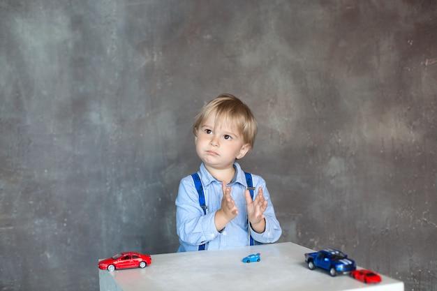 Het kind klapt in zijn handen. portret van een schattige kleine jongen die met auto's speelt. voorschoolse jongen spelen met speelgoedauto's in de kleuterschool. educatief speelgoed voor kleuters en kleuters.