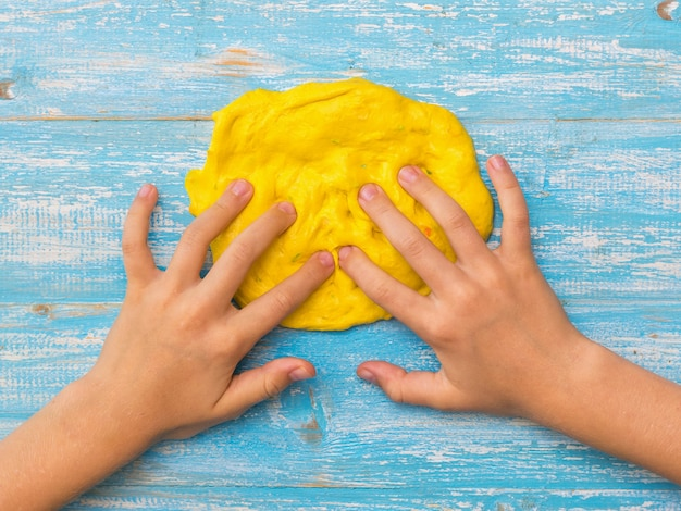 Het kind kneedt met zijn vingers een cirkel van geel slijm op een blauwe tafel