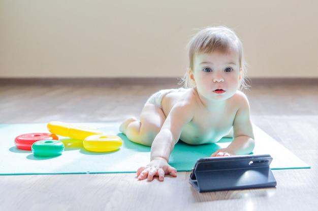 Het kind koos ervoor om met de telefoon te spelen in plaats van met speelgoed. meisje kijkt naar cartoon, speelgoed liggen rond. concept van reclame voor apparatuur, telefoons, educatieve spelletjes, kindertijd, kinderdag, kleuterschool