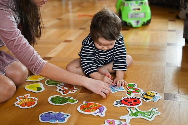 Het kind leert door middel van afbeeldingen. babyjongen en insecten. moeder en baby bestuderen insecten.