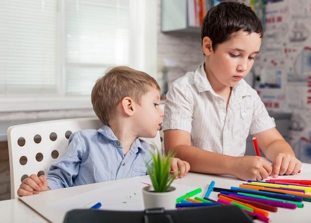Het kind leert thuis, gelukkige kinderen tekenen in de klas