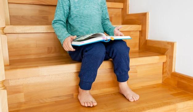 Het kind leest het papieren boek zittend op de houten trap in het huis