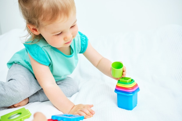 Het kind legt veelkleurig speelgoed in een stapel op de wieg