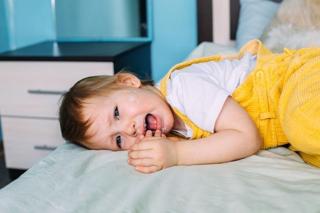 Het kind ligt ondeugend op bed te schreeuwen en te huilen
