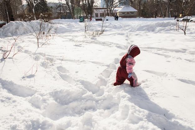Het kind loopt door het park waar veel sneeuw ligt