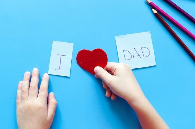 Het kind maakt de inscriptie ik hou van mijn vader uit letters en harten