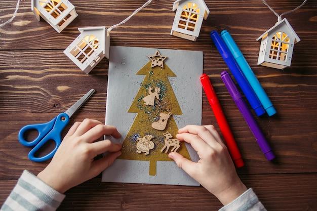 Het kind maakt een nieuwjaarskaart voor de wintervakantie