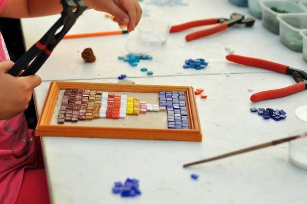 Het kind maakt een paneel van gekleurd glasmozaïek