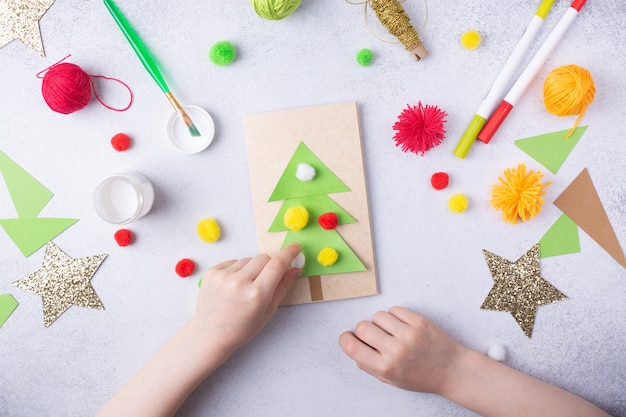 Het kind maakt een wenskaart kerstpapier collage kinderen kunstproject ambacht voor kinderen foto van hoge kwaliteit