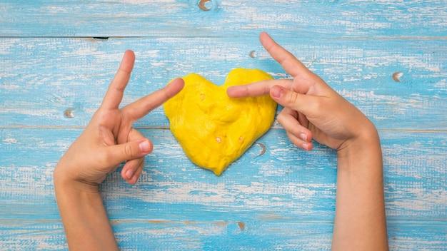 Het kind maakt gebaren met zijn vingers bij het hart van het gele slijm op een houten tafel