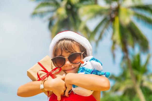 Het kind met kerstmanhoed en zonnebril het houden stelt bij het strand voor