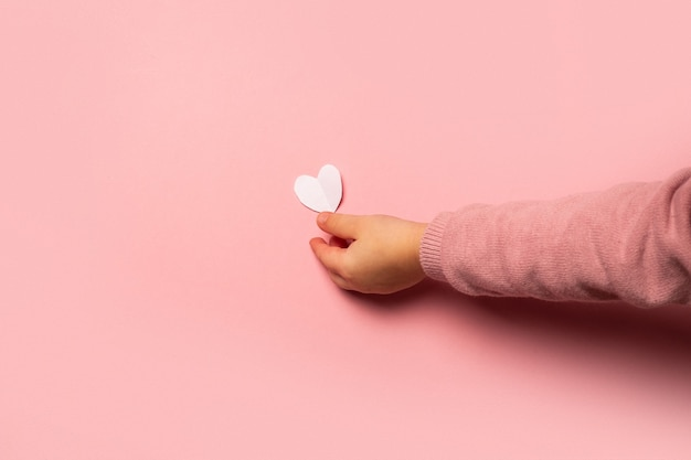 Het kind neemt een valentijnskaartkaart van document op een roze achtergrond. samenstelling valentijnsdag. banner. plat lag, bovenaanzicht.