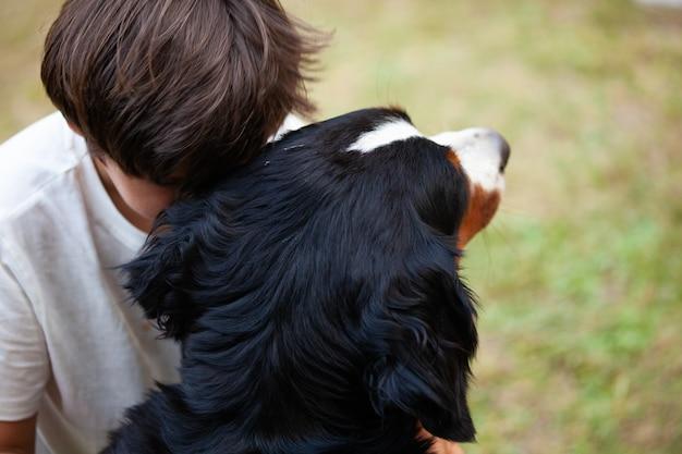 Het kind omhelst zijn hond terwijl hij zijn hoofd laat rusten als een teken van genegenheid en troost.
