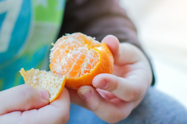Het kind pelt de schil van de mandarijn om te eten. gezond eten, nieuwjaarsstemming