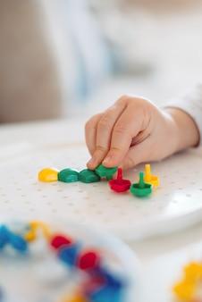 Het kind plakt het mozaïek met zijn vingers in de vorm.