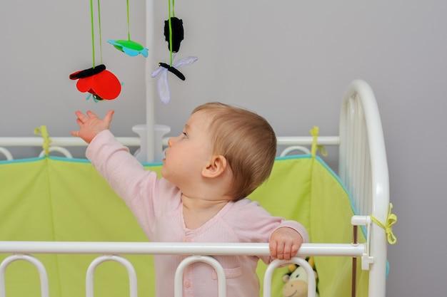 Het kind raakt mobiel hangend viltspeelgoed aan dier