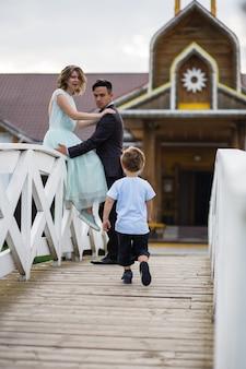 Het kind rent op de brug naar zijn ouders