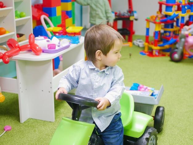 Het kind rijdt in een speelgoedauto. een kind speelt thuis met speelgoed. klein kind speelt met speelgoed in de kleuterschool. jongen in speelgoedauto