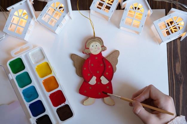 Het kind schildert kerstversieringsspeelgoed voor de kerstboom. diy-creativiteit met kinderen, concept