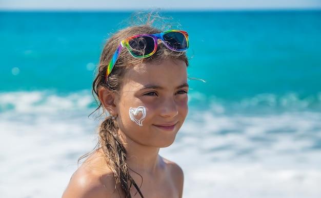 Het kind smeert zonnebrandcrème op haar gezicht. selectieve aandacht. kind.