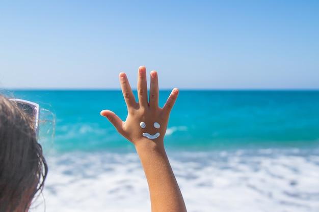 Het kind smeert zonnebrandcrème op haar hand. selectieve aandacht. kind.