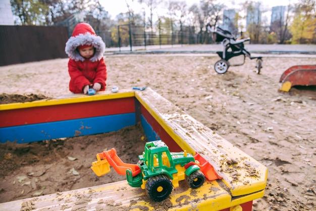 Het kind speelt auto's op de speelplaats