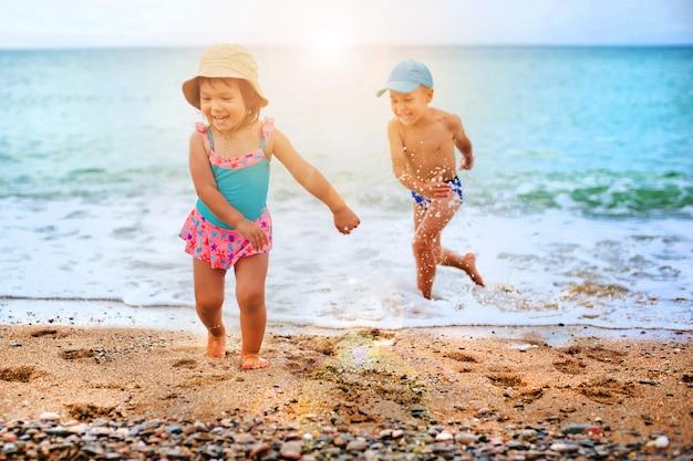 Het kind speelt en spettert in de zee