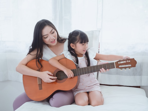 Het kind speelt in bed met haar moeder