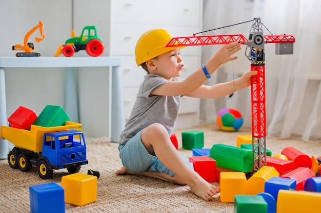 Het kind speelt in de bouwer in de kamer